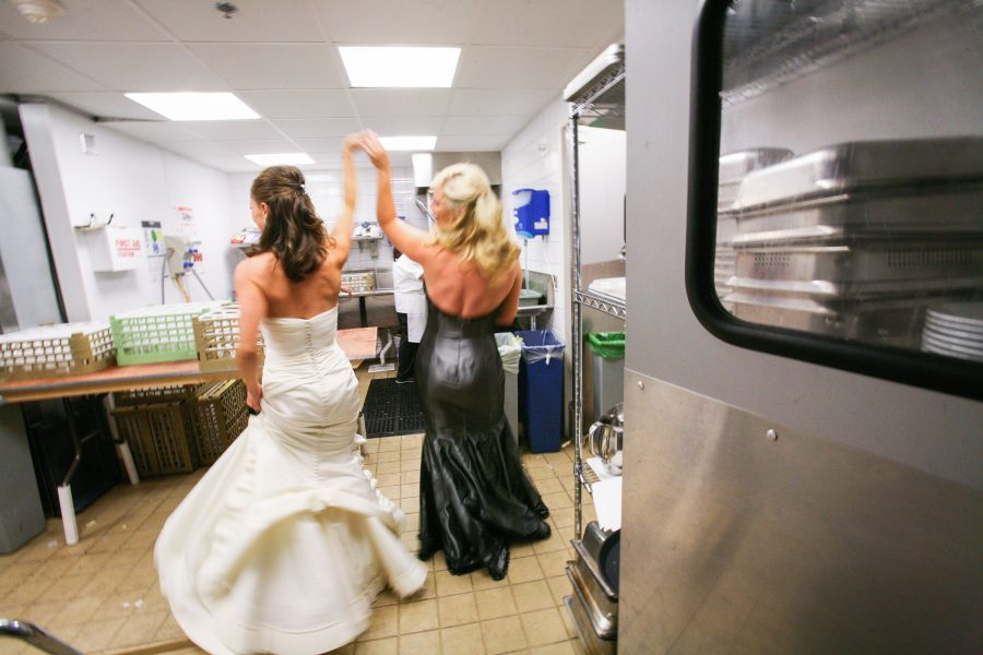 Bride and her bridesmaid dances into the kitchen at her wedding reception.